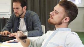 Regard de pensée potable de café de jeune homme d'affaires beau barbu loin banque de vidéos