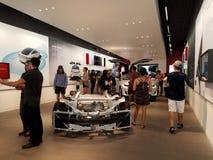 Regard de personnes aux voitures à l'intérieur du magasin de Tesla Photo stock