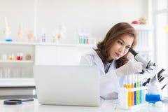 Regard de scientifique par le microscope photographie stock libre de droits
