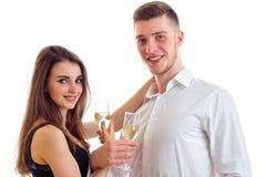 Regard de sourire de jeunes couples romantiques en avant et verres de transport de champagne d'isolement sur un fond blanc Photographie stock