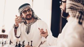 Regard deux arabe sur l'un l'autre et jouant aux échecs images libres de droits