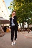 Regard du ` s de femmes à la mode avec la veste noire, le chemisier bleu et les espadrilles blanches Concept de mode Images libres de droits