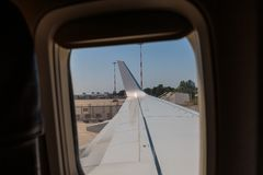 Regard en dehors d'une fenêtre d'une cabine d'aéronefs : Aile blanche d'avion Photos stock
