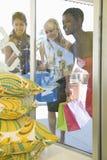Regard femelle de clients aux coussins par la fenêtre de boutique Photos stock