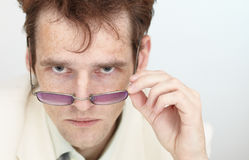 Regard grave de jeune homme au-dessus des lunettes Image libre de droits
