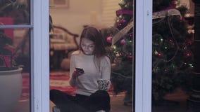 Regard mignon de fille dans le téléphone près de l'arbre de Noël clips vidéos
