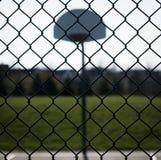 Regard par le terrain de basket éclairé à contre-jour par barrière Image libre de droits