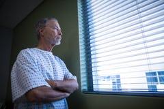 Regard patient en difficulté par des abat-jour de fenêtre photo stock