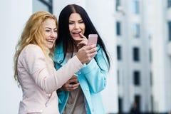 Regard riant d'amies au téléphone Photo libre de droits