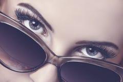 Regard séduisant au-dessus des lunettes de soleil Image libre de droits