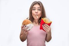 Regard stupéfait de jeune femme sur la caméra et manger les pommes de terre frites Elle tiennent l'hamburger dans des mains aussi photo stock