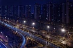 Regard sur le gratte-ciel dans une rangée et une autoroute par nuit Image stock