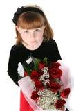 Regard vers le bas sur une petite fille mignonne avec les roses rouges photos stock
