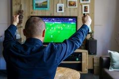 Regardant un match de football important à la maison photographie stock