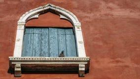 Regardant un vieux châssis de fenêtre de stuc baigné dans la lumière, avec des châssis de fenêtre blancs et un pigeon été perché  Photographie stock