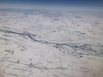 Regardant vers le bas du ciel, de la terre couverte de neige et du blanc sont empilés photographie stock