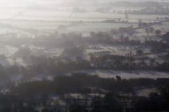 Regardant vers le bas sur des champs et des fermes le lever de soleil sur un froid, givré, brumeux, jour d'hivers images libres de droits
