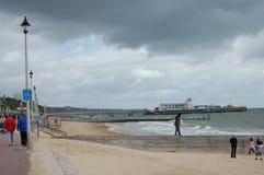 Regarder en bas de la plage des brise-lames qui est saillante dans la mer Le pilier de Bournemouth est dans la distance Photographie stock