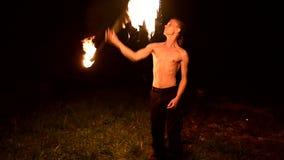 Regarder l'appareil-photo Le jeune mâle avec de longs cheveux et torse nu tourne l'extérieur brûlant de torche sur un mouvement l clips vidéos