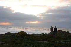 Regarder le coucher du soleil des roches Photographie stock