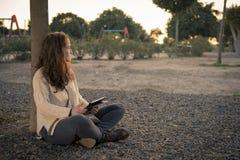 Regarder le coucher du soleil se reposant à côté d'un arbre Photographie stock libre de droits