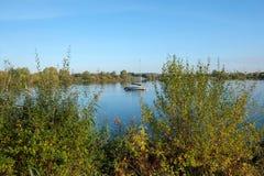 Regarder par les buissons le voilier a amarré sur le lac Photographie stock libre de droits