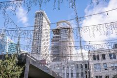 Regarder par les quirlandes électriques et l'éclairage extérieur le skyscrap Photographie stock