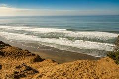 Regarder vers le bas les ressacs Pacifiques d'une falaise arénacée dans le Ca Photo libre de droits