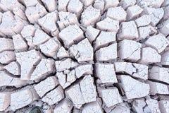 Regarder vers le bas sur la boue blanche grise criquée sèche formant des modèles le fond d'un lit de rivière images libres de droits