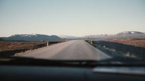 Regardez à l'intérieur de la voiture par le pare-brise sur la belle route de campagne avec le beau coucher du soleil, montagnes a Photo stock