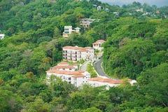 Regardez aux hôtels les bâtiments dans la forêt tropicale dans Quepos, Costa Rica Photographie stock
