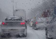 Regardez de la voiture de la chute de neige importante cause le problème du trafic sur la route congelée d'hiver image stock