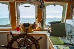 Regardez la carlingue capitan de cuvette avec le volant sur le bateau Photos libres de droits