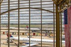 Regardez la fenêtre d'aéroport aux avions et aux opérations de rampe Photographie stock