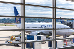 Regardez la fenêtre d'aéroport aux avions et aux opérations de rampe Images stock