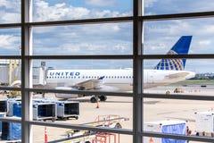 Regardez la fenêtre d'aéroport aux avions et aux opérations de rampe Photo libre de droits