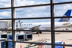 Regardez la fenêtre d'aéroport aux avions et aux opérations de rampe Image libre de droits