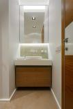 Regardez le miroir sur l'évier dans une salle de bains moderne Image libre de droits