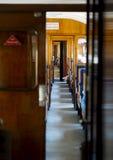 Regardez le regard en bas d'un chariot de train avec les sièges en bois Photo stock