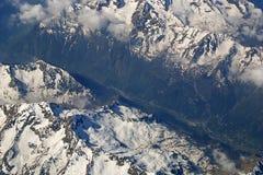 Regardez le regard vers le bas sur les montagnes couvertes par neige du siège d'avion Images stock