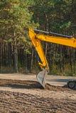 Regardez le scoop de l'exkavator sur la terre dans la forêt photos stock