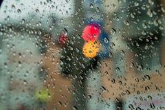 Regardez les feux de signalisation par le verre humide de la voiture