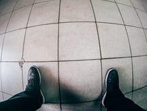 Regardez vers le bas sur des jambes dans des espadrilles noires se tenant sur le plancher carrelé Photos libres de droits