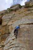 Regards de grimpeur de roche vers le bas avec le sourire Images stock