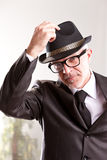 Regards miss mistress or mister. A fifties style retro businessman rising his hat to salute you Stock Photo