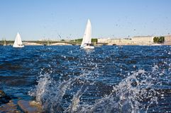 Regatta. Yacht regatta in the downtown of Saint-Petersburg, Russia. The waves are breaking over the river bank Royalty Free Stock Photos