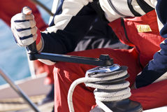 Regatta Details. Detail of a man working with hands and gloves on the winch of a sailboat during Regatta Barcolana - (Trieste, Italy 2007 Royalty Free Stock Photo