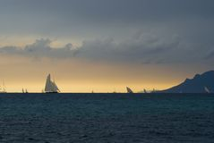 Regattas under  storm. Old sailboats  in Cannes bay during les Regates Royales in September 2008. The weather was stormy with a very strange  light above the Stock Photos
