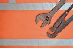 Regelbare en pijpmoersleutels tegen de achtergrond van een oranje overhemd van de signaalarbeider Stilleven verbonden aan reparat stock fotografie