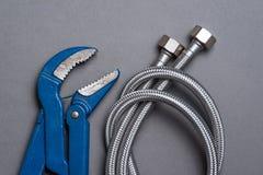 Regelbare moersleutel en de gevlechte slang van het roestvrij staalwater Stock Fotografie